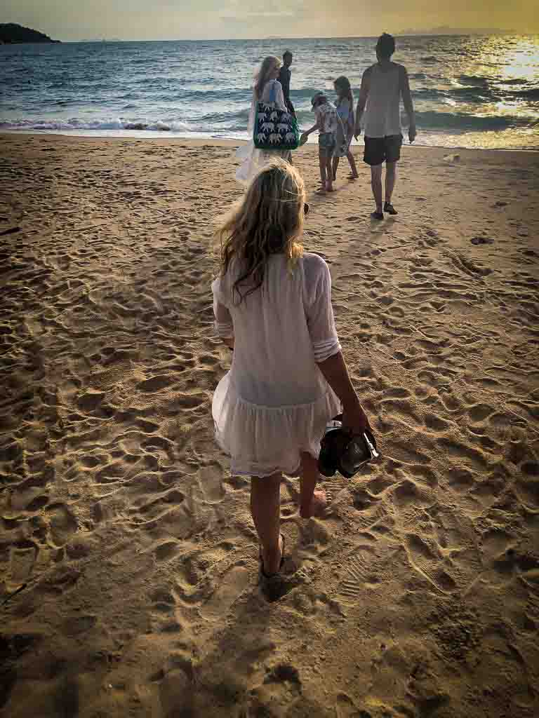 karen quinn with her back to the camera in a white dress walking towards her family at the sea