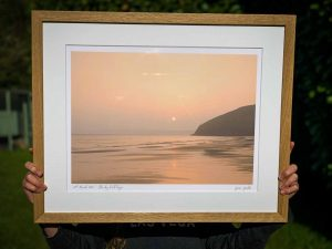 beautiful photo of the sunrise on a beach in cornwall with a wooden frame